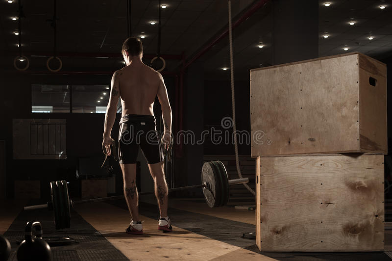 Young muscular man exercising with barbell. Male athlete with naked torso doing weightlifting workout. Sports, fitness - healthy lifestyle concept stock images