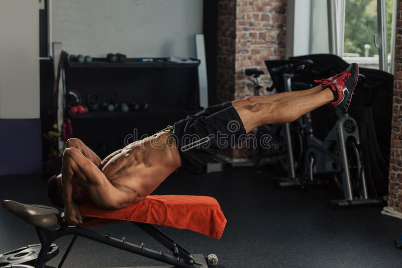 Young muscular man in the gym doing exercise royalty free stock photography