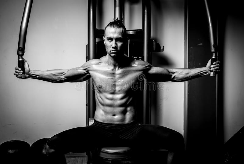 Young muscular man in gym. Doing exercise. Showing his muscles. Black and white royalty free stock image