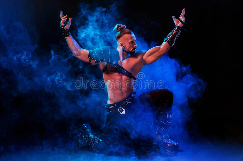 Young and muscular man performing a theatrical pose on stage. Young and muscular man performing a theatrical pose on a stage. Very man in stage costume stock photo