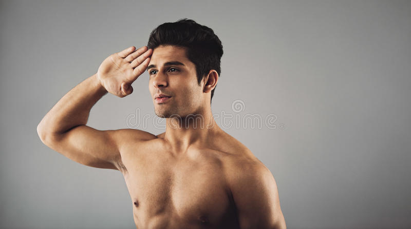 Young muscular man saluting. Portrait of young muscular man saluting. Masculine young man doing a salute over grey background with copyspace stock photos