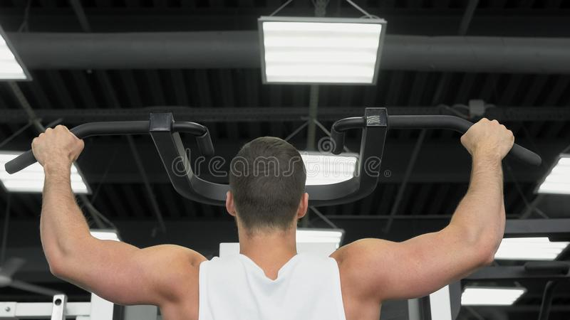 Young muscular man trains at the gym. athlete of weight training royalty free stock photography