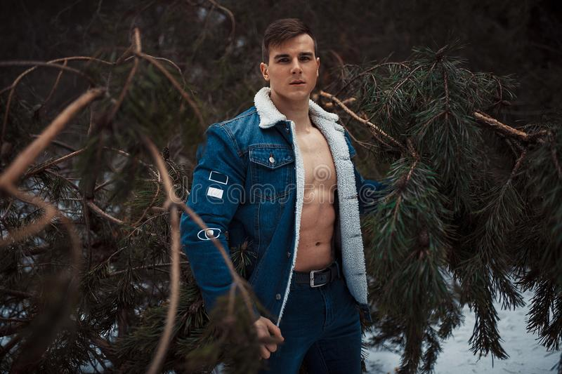 Young muscular man in unbuttoned jacket with bared breast stands next to pine tree in winter forest. royalty free stock image