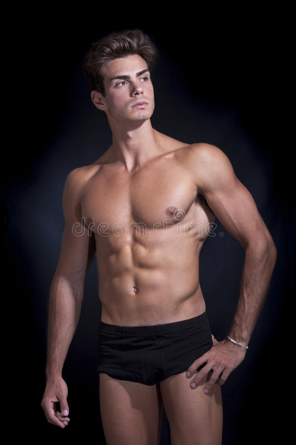 Young muscular man in underwear with a black background. And dark blue light point. A man is in intimate Italian dressing shorts. The boy has a physical royalty free stock photo