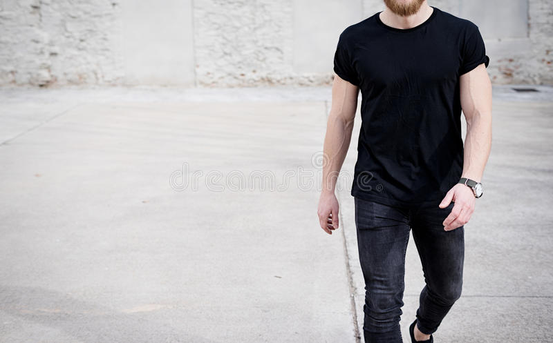 Young muscular man wearing black tshirt and jeans walking on the urban district. Blurred background. Hotizontal mockup. Young muscular man wearing black tshirt royalty free stock images