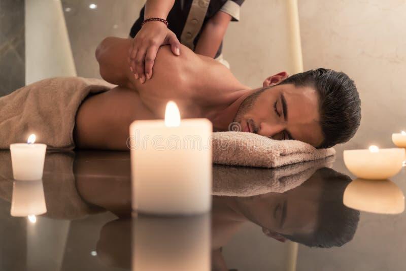 Young man enjoying the healing benefits of traditional Thai massage royalty free stock photos