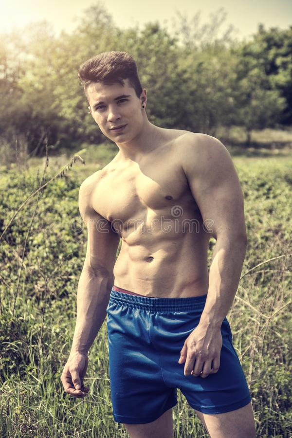 Young Muscular Shirtless Hunk Man Outdoor in Nature. Handsome Muscular Shirtless Young Hunk Man Outdoor in Nature Standing on Grass. Showing Healthy Muscle Body royalty free stock images