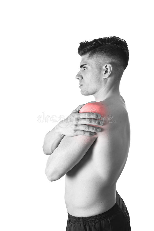 Young muscular sport man holding sore shoulder in pain touching massaging in workout stress. Young muscular sport man holding sore shoulder with hand touching or royalty free stock photography
