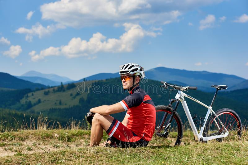 Sportsman cyclist in professional sportswear and helmet sitting near his bicycle on grassy roadside. Young sportsman cyclist in professional sportswear and royalty free stock photos