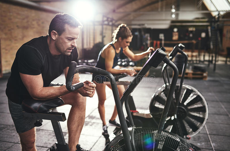 Young muscular sportspeople training on simulators royalty free stock photo
