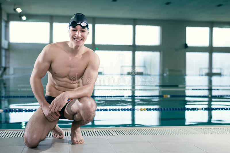 Young muscular swimmer with goggles and swim cap. Ready for action, looking at the camera and smiling. Horizontal shot, copy space stock photo