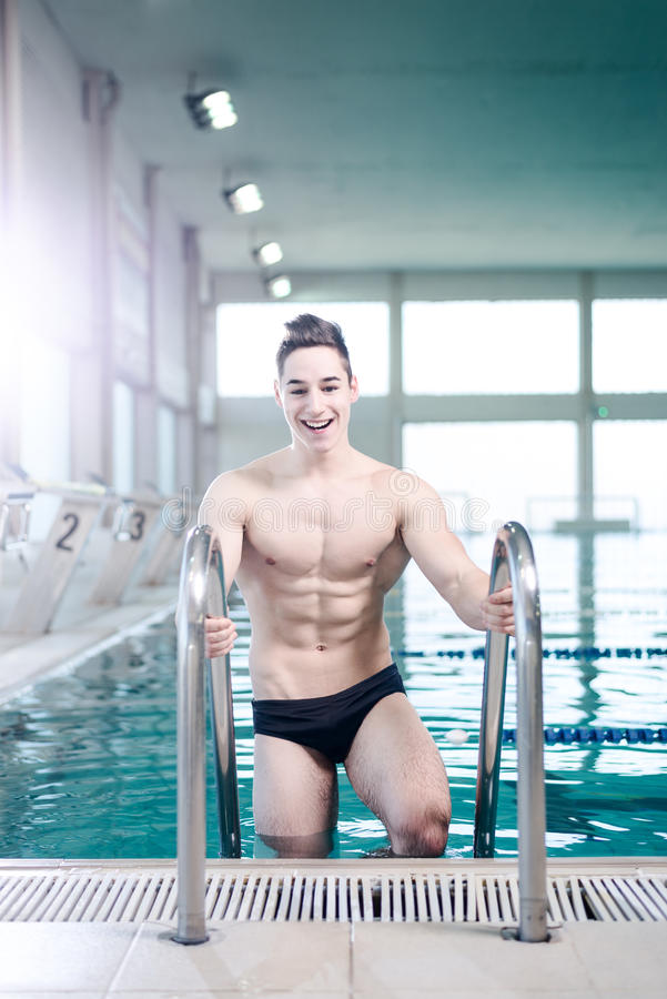 Young muscular swimmer on the ladder royalty free stock images