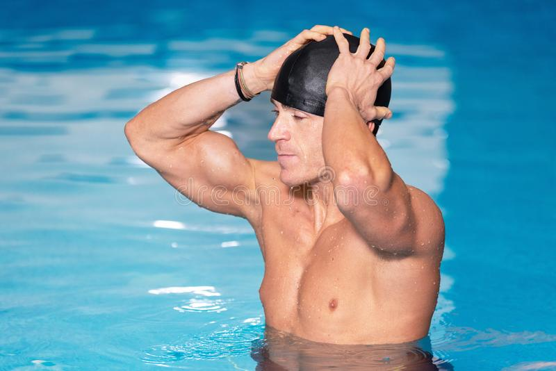 Young muscular swimmer preparing to swim, putting his cap on. royalty free stock photos