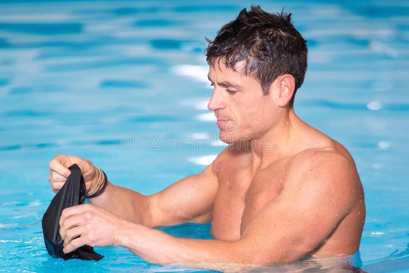 Young muscular swimmer preparing to swim, putting his cap on. Young muscular swimmer preparing to swim, putting his cap on stock photo