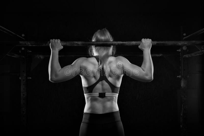 Young muscular woman doing pull up exercise in gym royalty free stock images