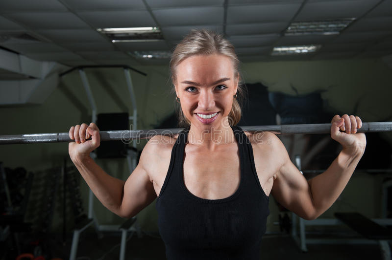 Young muscular woman doing workout. At the gym royalty free stock photo