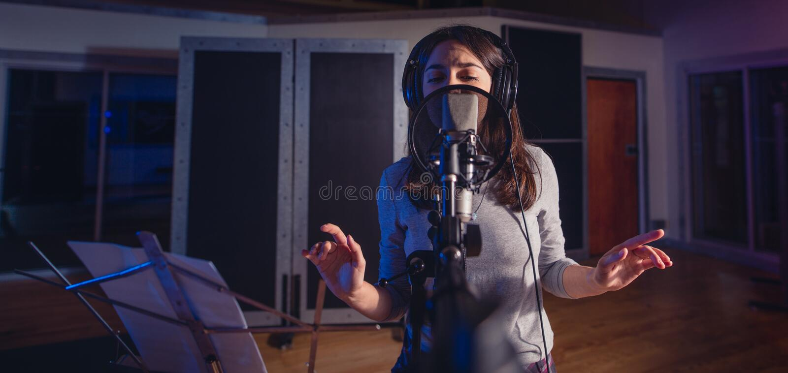 Female singer singing a song in recording studio royalty free stock image