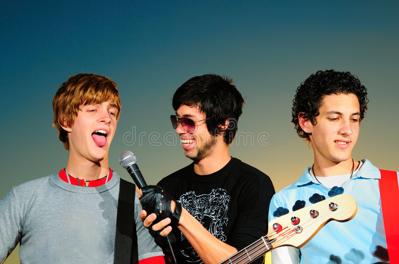 Young musical band. Portrait of three young musicians playing together stock images
