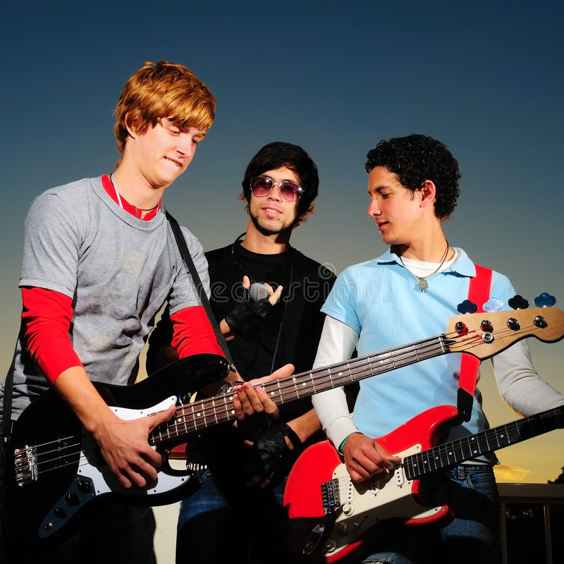 Young musical band. Portrait of young trendy musicians playing electric guitars stock images