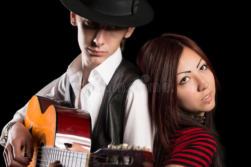 Young musical couple. On a black background. Asian women and Caucasian man stock photography