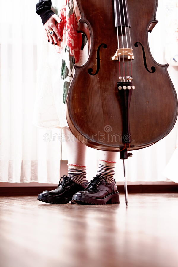 Young musician. Young female cellist wearing flat shoes and striped socks stood beside a cello resting on its spike royalty free stock image