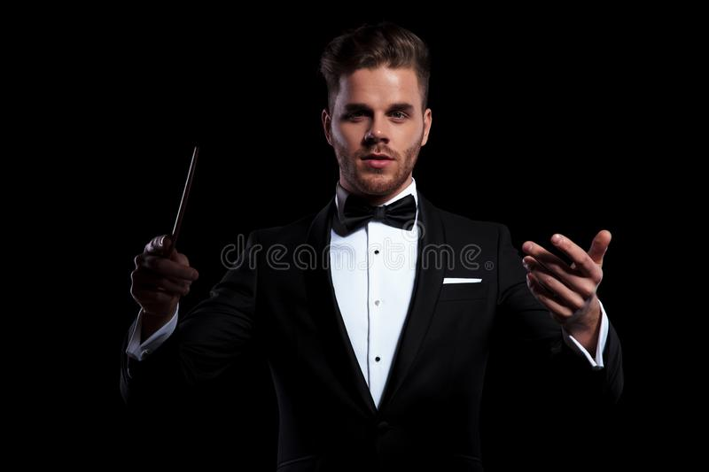 Young musician conducting using a stick and gesturing. Front view of young musician conducting using a stick and gesturing on black background stock images