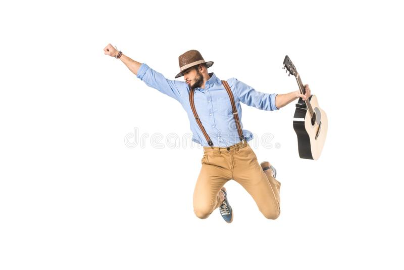 young musician in hat holding guitar and flying with raised hand stock image