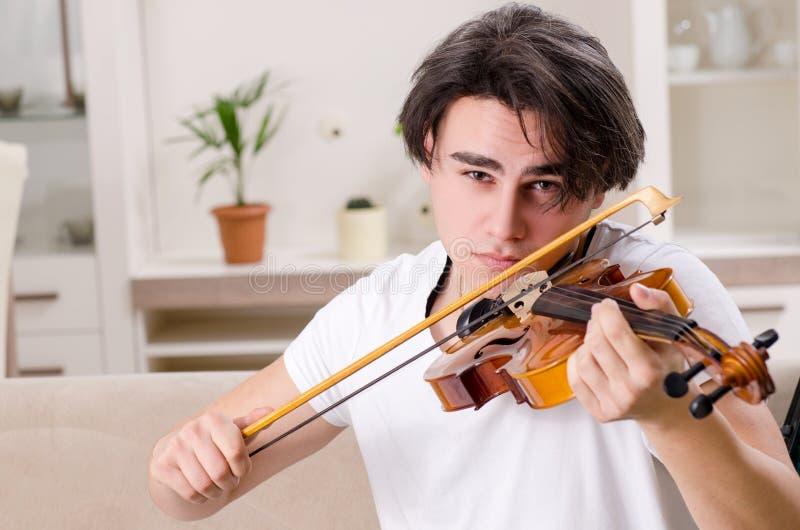 Young musician man practicing playing violin at home. The young musician man practicing playing violin at home royalty free stock image