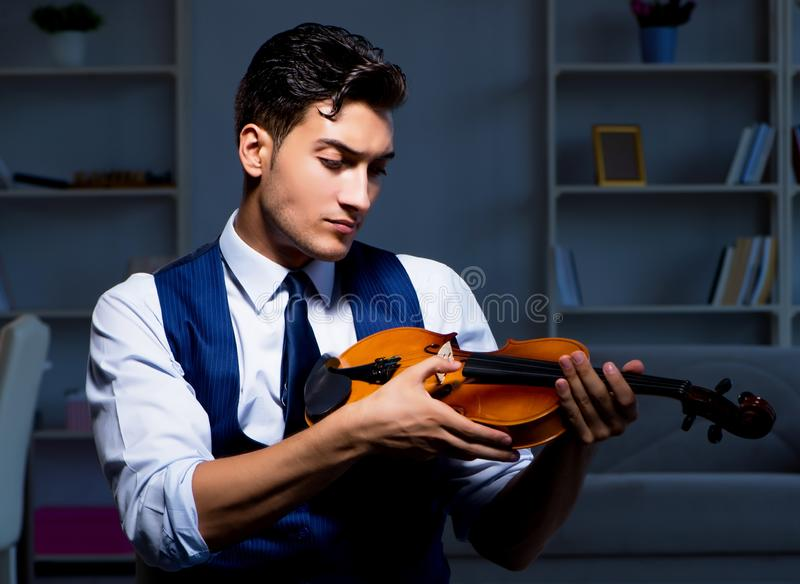 Young musician man practicing playing violin at home. The young musician man practicing playing violin at home royalty free stock photos