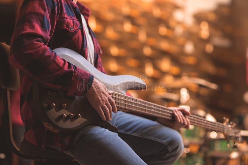 Young musician playing bass guitar. Close-up stock photography