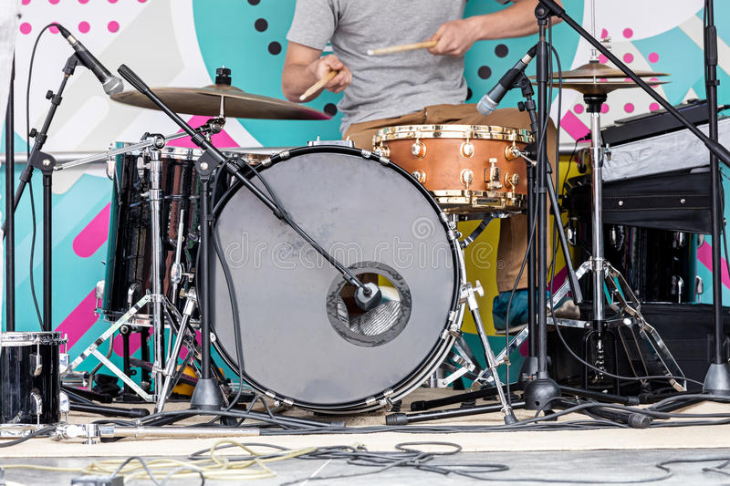 Young musician playing drums on outdoor stage during the music f stock photos