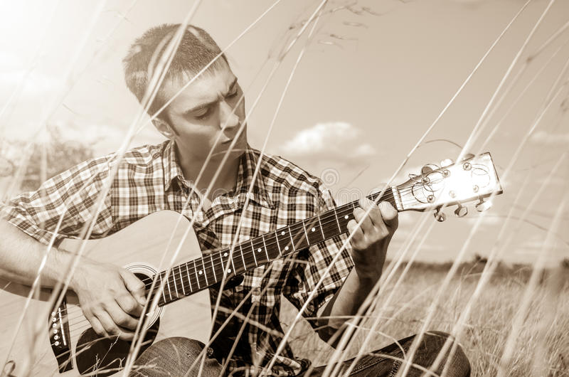 Young musician playing guitar in nature. Young musician playing guitar among high grass - monochrome royalty free stock photos