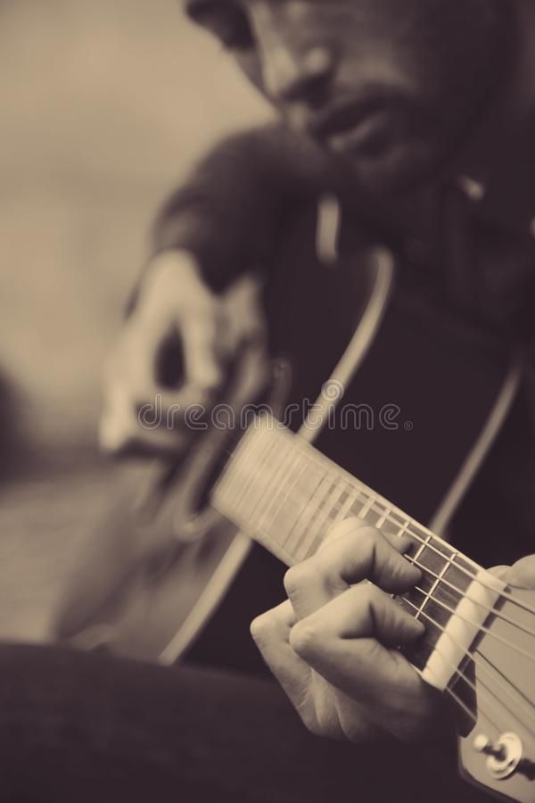 Young musician playing guitar on the streets of old European cit stock images