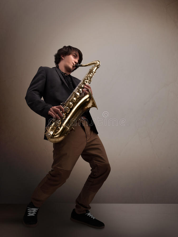 Young musician playing on saxophone. Handsome young musician playing on saxophone royalty free stock photo