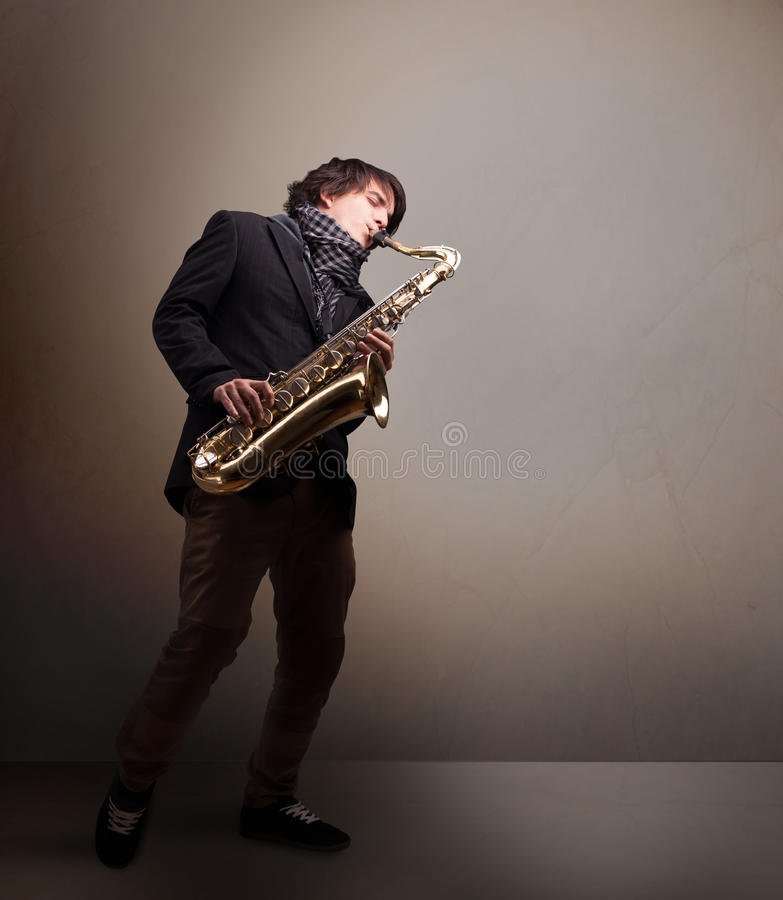 Young musician playing on saxophone. Handsome young musician playing on saxophone stock photo