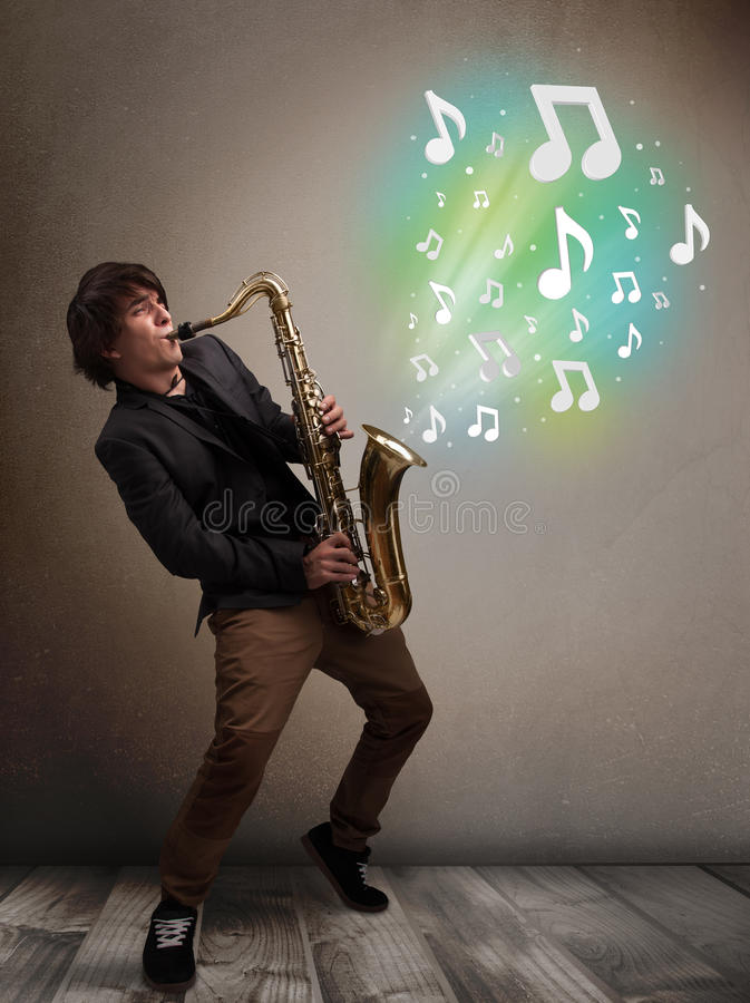 Young musician playing on saxophone while musical notes exploding royalty free stock image