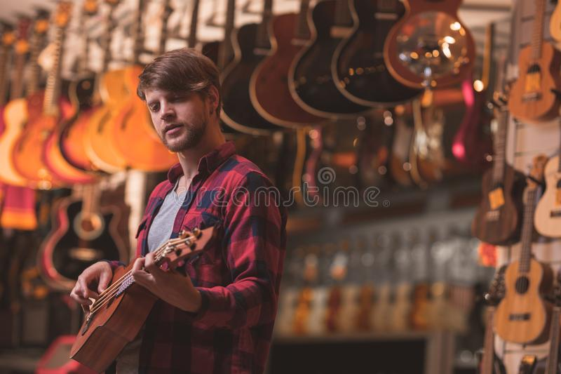 Young musician playing on a ukulele in a music store. Young man playing on a ukulele in a music store royalty free stock image