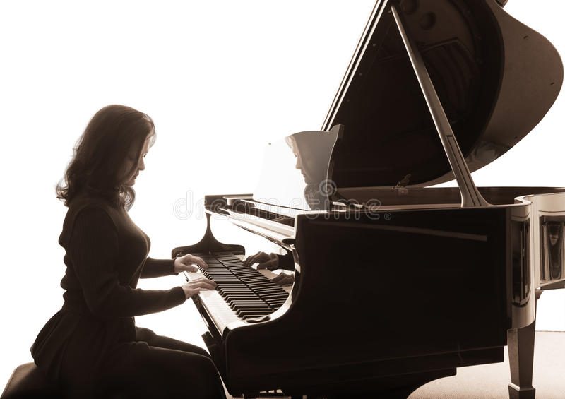 Young musician plays the grand piano. Square composition stock images