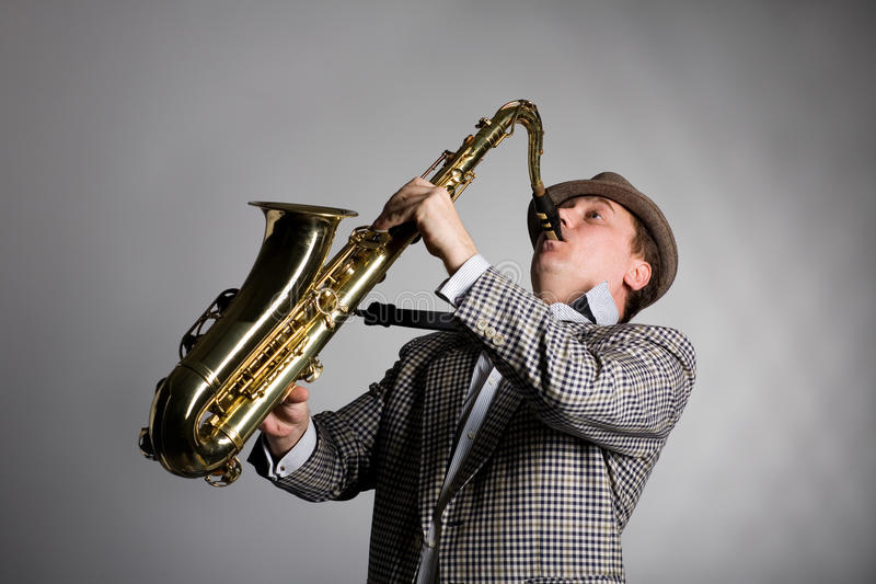 Young musician plays the saxophone. Young musician in a checkered jacket, plays the saxophone stock images