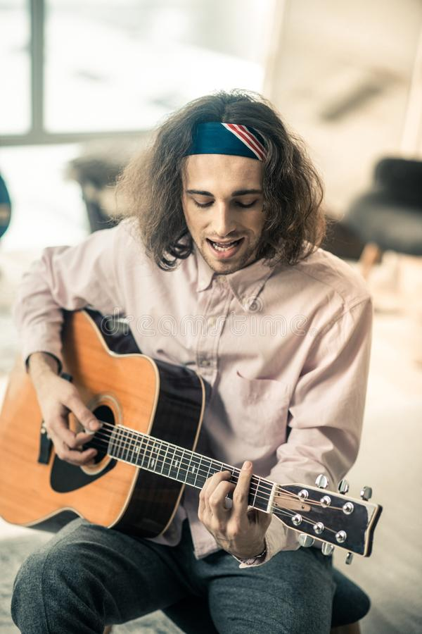 Concentrated dark-haired man singing lyric song and accompanying. Young musician practicing. Concentrated dark-haired man singing lyric song and accompanying royalty free stock photography