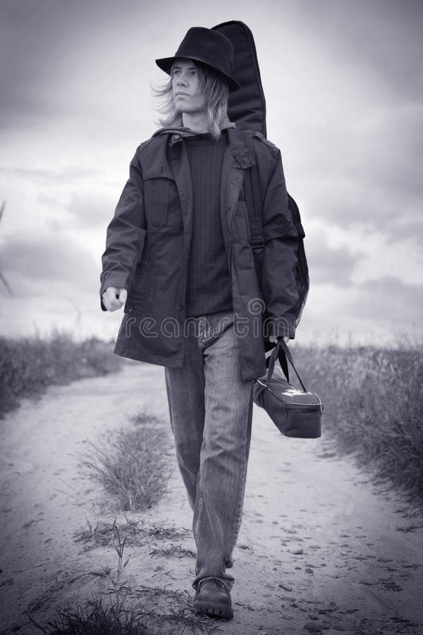 Young musician walking. Full body portrait of a young musician walking on the field stock photo