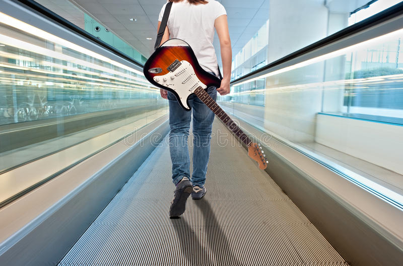 Young musician woman with electric guitar. Young musician woman with an electric guitar on the airport travelator royalty free stock images