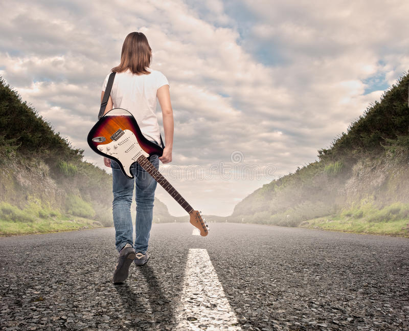 Young musician woman walking on a road. Young musician woman with an electric guitar walking on a road royalty free stock photography