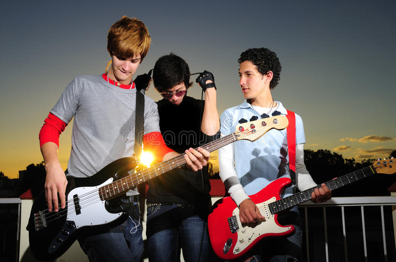 Young musicians posing with instruments. Portrait of young hispanic musical band posing at sunset royalty free stock images