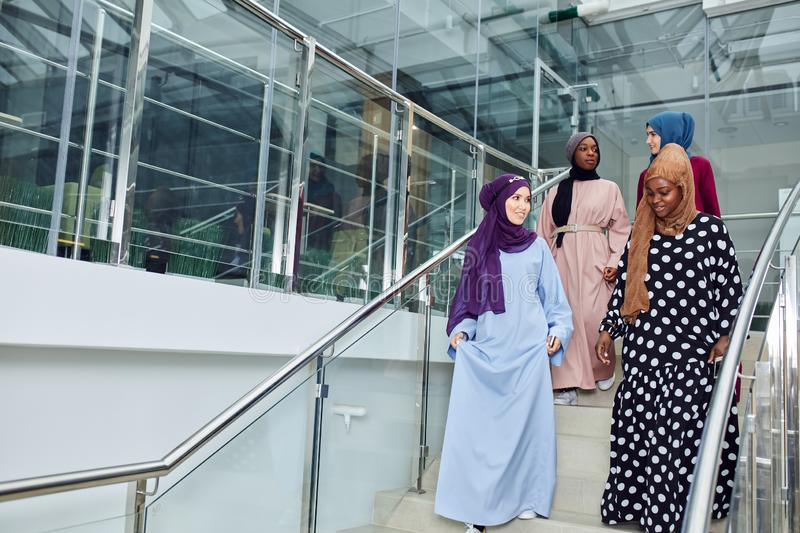Group of four muslim girls walking at stairs of shopping mall royalty free stock image