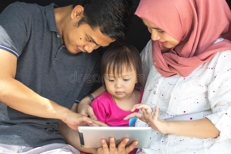 Young muslim family , transport, leisure, road trip and people concept - close up portrait of happy man, woman and little girl stock image