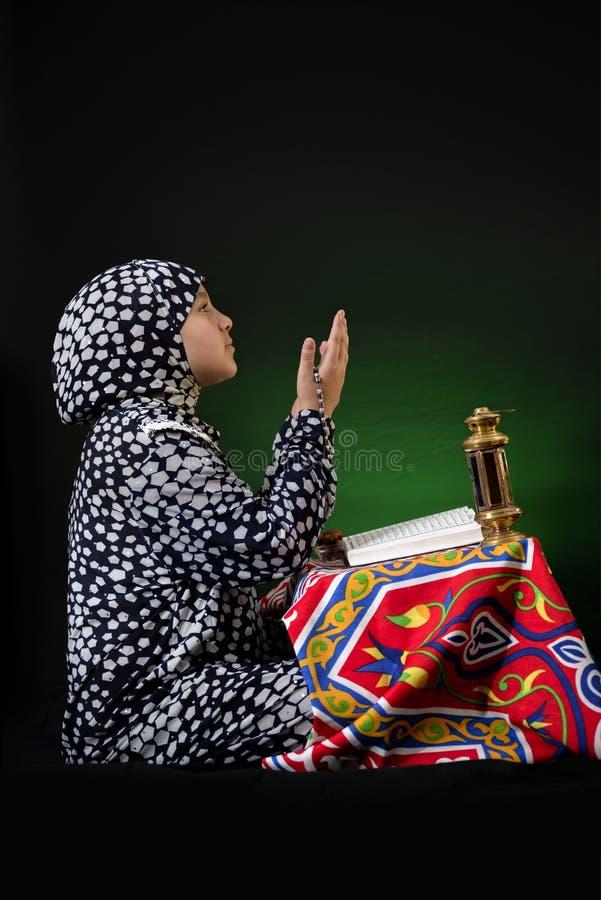 Young Muslim Girl Praying with Ramadan Objects stock image