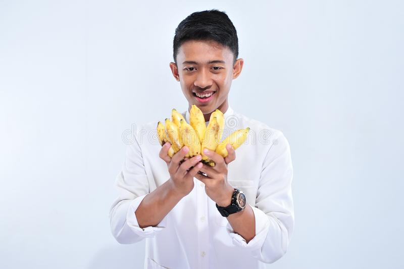 Young muslim man happy fasting when breaking the fast Iftar and suhoor eat yellow banana stock photography