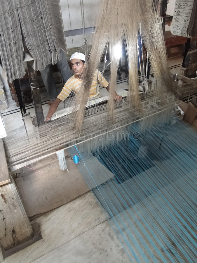 Young muslim man runs a loom to weave silk brocade stock photo