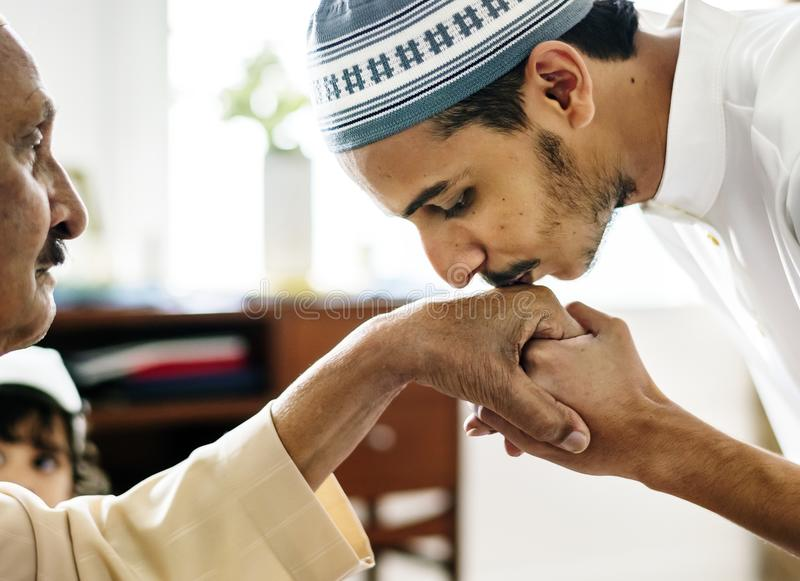 Young Muslim man showing respect to his father. Young Muslim men showing respect to his father stock images
